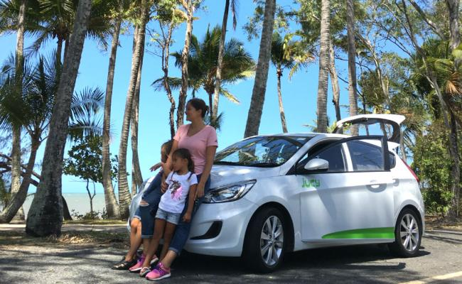 family stands in front of jucy car