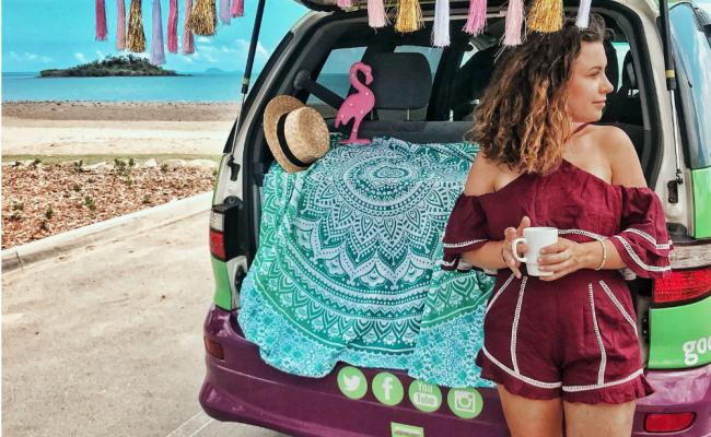 girl drinking tea in back of juc van with hippie decorations