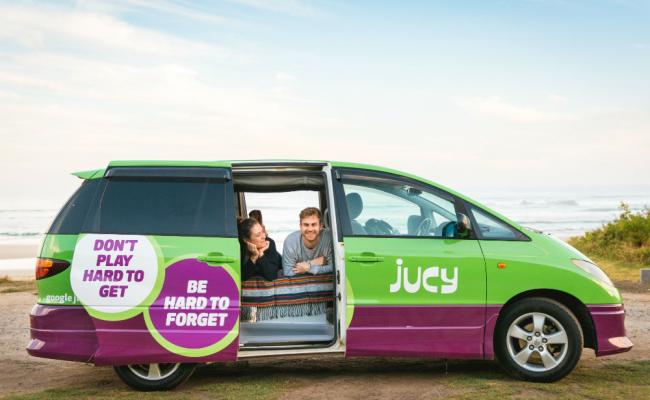 two people in a bed in the back of a jucy campervan