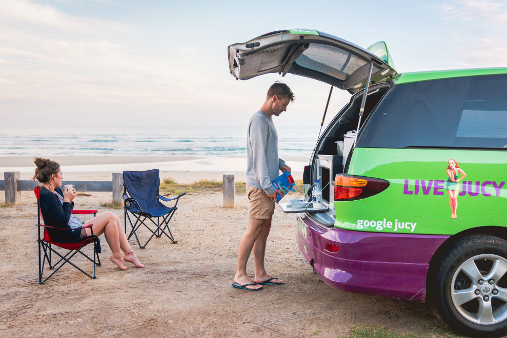 couple cooks dinner in the back of jucy campervan