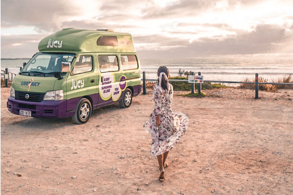 girl in sundress twirls in front of jucy vehicle