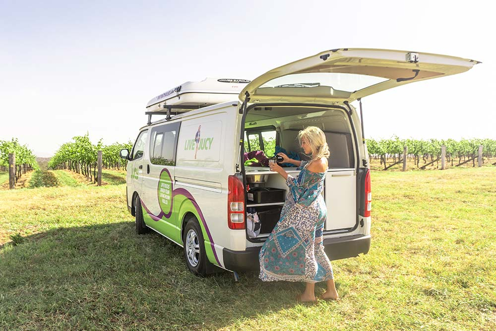 girl prepares food in the kitchen of a jucy campervan in australia