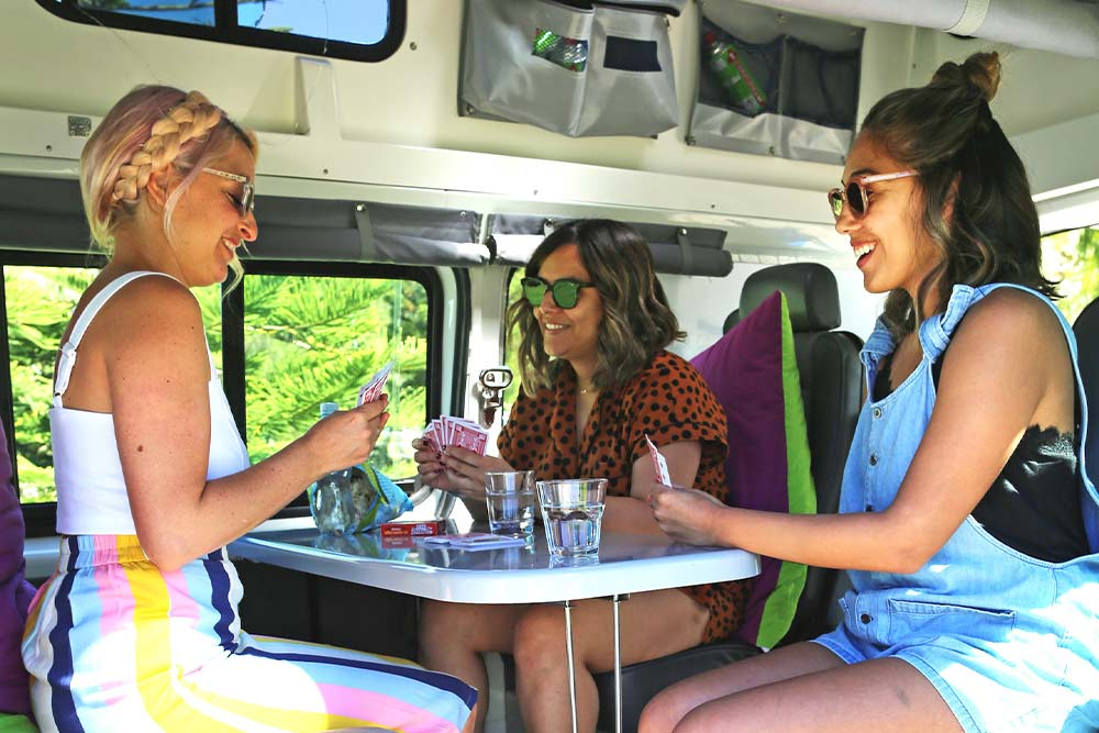 girls playing cards in a jucy van in australia